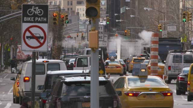 crowded new york city street filled with cars and pedestrians. steam tossed by the wind moves about. - road sign stock videos & royalty-free footage