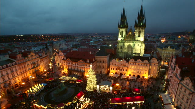 Crowded Old Town Square in Prague at night during Christmas season