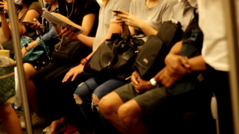 crowded people in the mass public transportation using their phone while waiting - rail transportation stock videos & royalty-free footage