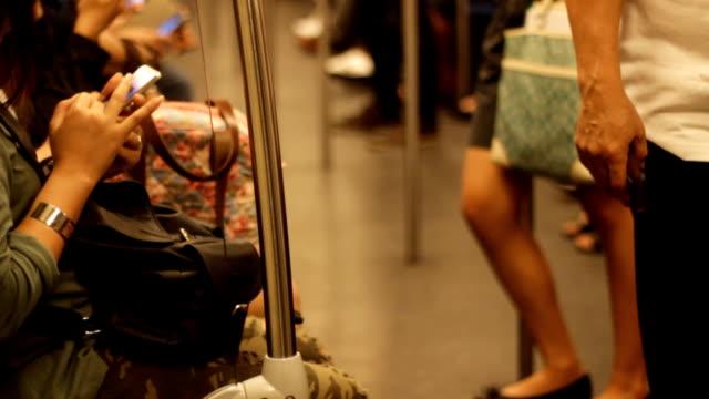 Drukke mensen in de massa openbaar vervoer met behulp van hun telefoon terwijl we wachten