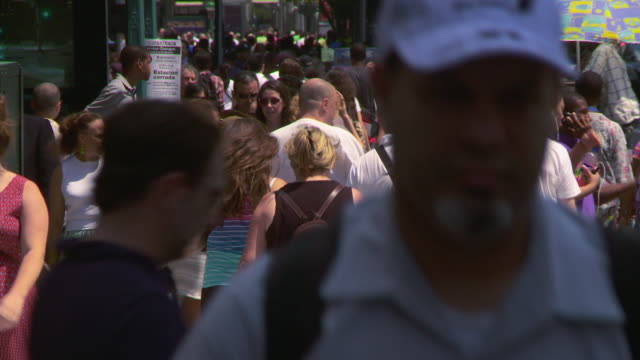 a crowded side walk with tourists on 8th ave by penn station in new york city - new york city penn station stock videos and b-roll footage