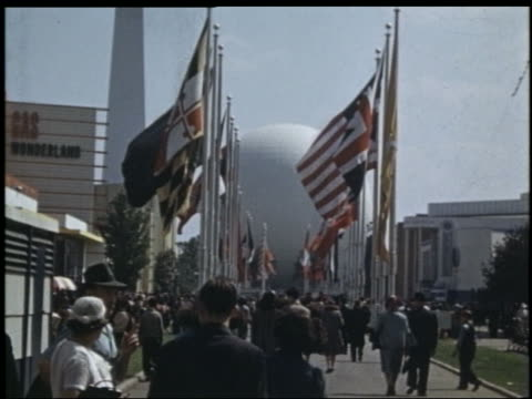 vídeos de stock, filmes e b-roll de crowded sidewalk lined with flags / large white sphere in background / new york world's fair - world's fair de nova york
