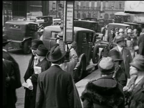 B/W 1927 crowded sidewalk / woman taking bus transfer from box / traffic in background / Paris, France