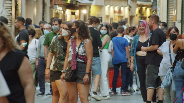 crowded street at spain full of young people during summer 2021. some of them wearing masks - spanish culture stock videos & royalty-free footage