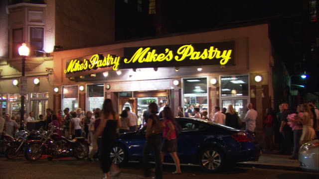 WS Crowded street in front of Mike's Pastry shop at night, 300 Hanover Street, North End, Italian neighborhood / Boston, Massachusetts, USA