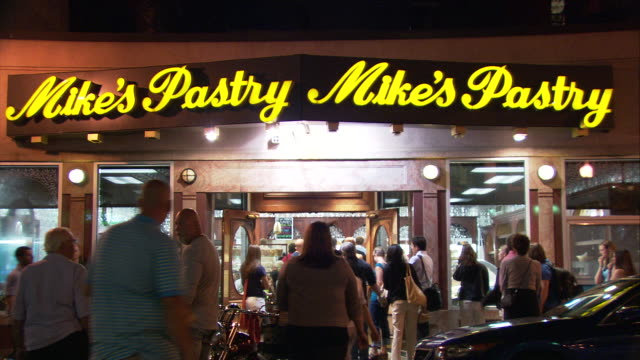 stockvideo's en b-roll-footage met ms crowded street in front of mike's pastry shop at night, 300 hanover street, north end, italian neighborhood / boston, massachusetts, usa - westers schrift