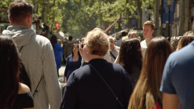 crowded street in slow motion. barcelona ramblas famous street establishing shot filmed slow motion with telephoto lens with defocused crowd - telephoto lens stock videos and b-roll footage
