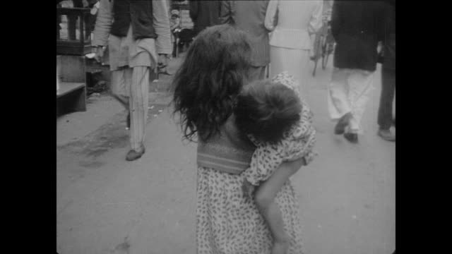 Crowded streets of an Indian city where orphaned children carrying barefoot siblings contrast with the suited businessmen