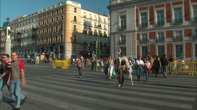 ws pan crowded streets with monument to king charles iii, puerta del sol, madrid, spain - 横断歩道点の映像素材/bロール