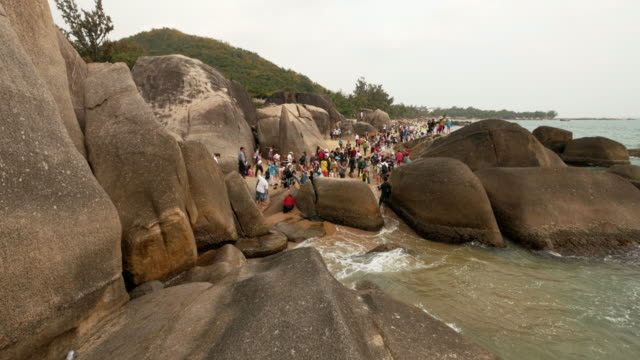 crowded tourist attraction end of the world (tian ya hai jiao) 天涯海角 in sanya,  hainan province, china. extreme wide shot - spoonfilm stock-videos und b-roll-filmmaterial
