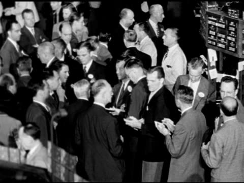 Crowded trading floor near booth men w/ notebooks MS Exchange Recorder setting agreed selling price numbers by hand 'page boy' fingers placing...