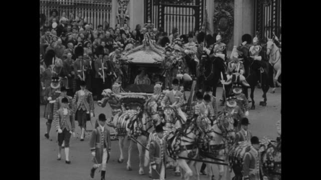 crowds and the queen's guard line the victoria memorial as the procession proceeds / elizabeth ii and prince philip in the gold coach / footmen and... - royal navy stock videos and b-roll footage
