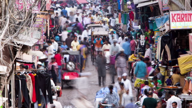 tl, ha, ls crowds and traffic swarm through delhi's old town bazaar / delhi, india - risciò video stock e b–roll
