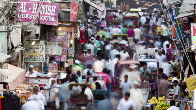 vídeos de stock, filmes e b-roll de tl, ha crowds and traffic swarm through delhi's old town bazaar / delhi, india - time lapse de trânsito
