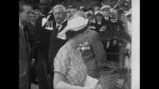 ms crowds both black and white in front of grass covered arch that says long live the queen / queen elizabeth walks with dignitary past veterans on... - 1953 stock videos and b-roll footage