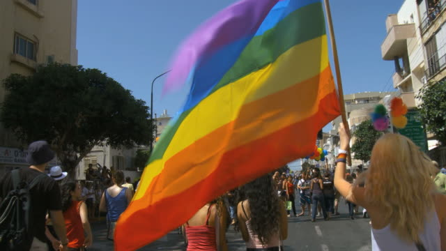 ms pov crowds celebrate and wave flags at gay pride in streets / tel aviv, israel - marciare video stock e b–roll