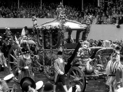 stockvideo's en b-roll-footage met crowds cheer as the queen leaves westminster abbey in the gold state coach 1953 - yeomen warder