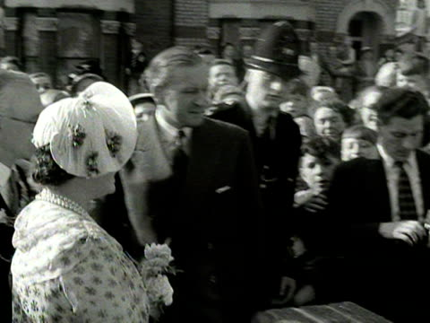 crowds cheer as the queen mother arrives at a terraced house in fulham for a tour of the owners garden 1954 - queen dowager stock videos and b-roll footage