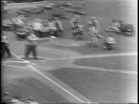 vídeos y material grabado en eventos de stock de crowds cheer in the stands at the new york polo grounds / a male dwarf performer runs out to bat as part of a comedic softball game staged by... - enano