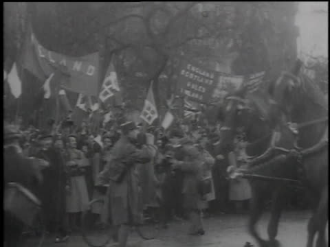 crowds cheering and waving flags as dignitaries ride past in horse-drawn carriages / paris, france - 1918 stock videos & royalty-free footage