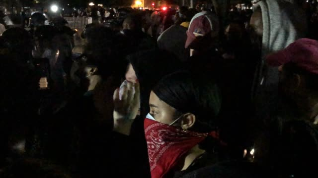 crowds complain about the situation as police behind protective shields hold a perimeter as demonstrators gather to protest the killing in... - protestor stock videos & royalty-free footage