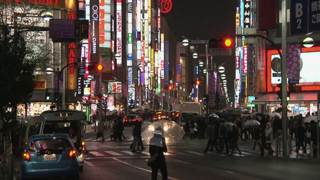 ws crowds cross zebra crossing on shinjuku street at night / tokyo, kanto, japan - 日本語の文字点の映像素材/bロール