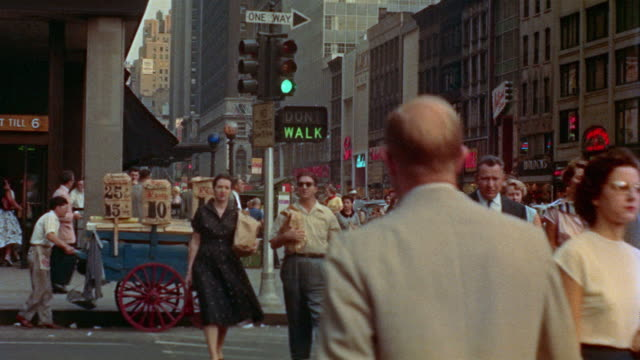 stockvideo's en b-roll-footage met 1955 ms crowds crossing 7th avenue at 34th street / tu empire state building / new york city - 1955