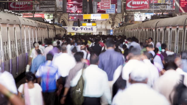 TL, LS Crowds disembark from trains in Victoria Terminus Railway Station / Mumbai, India