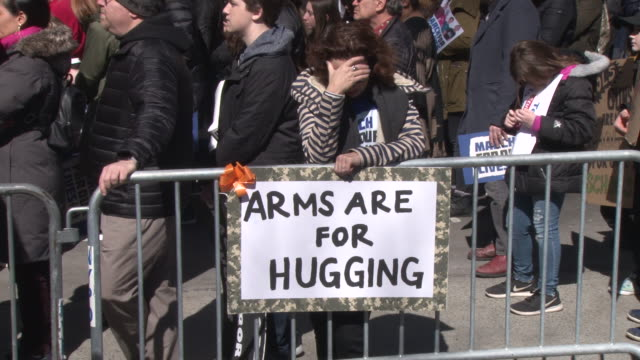 crowds display their signs of protest while waiting for march to begin / thousands of people many of them students march against gun violence in... - march for our lives stock videos and b-roll footage