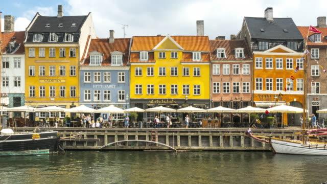 tl:コペンハーゲン・ニューハウン市のカラフルな伝統的な家の中で新鮮な日の下でレストランバーを楽しむ群衆、デンマーク - オーレスン地域点の映像素材/bロール