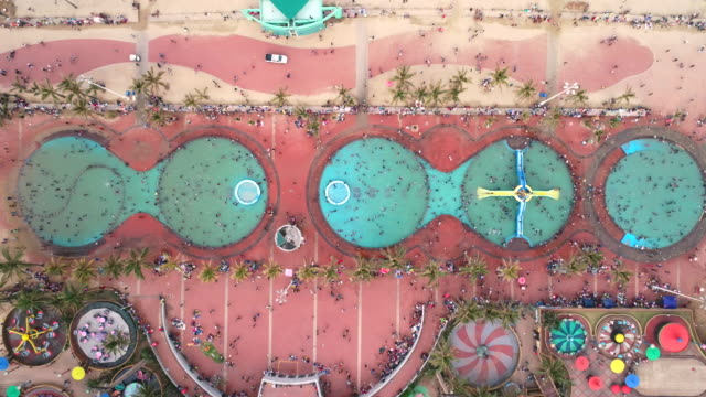 crowds enjoying the pools and water-slides at an amusement on the durban beachfront - roundabout stock videos & royalty-free footage