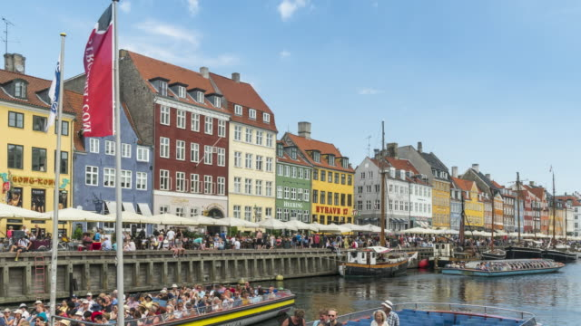 tl: crowds enjoying traveling by boat in morning among colorful traditional houses in copenhagen nyhavn city, denmark - copenhagen video stock e b–roll