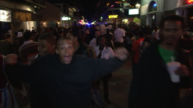 crowds fill bourbon street at night. - bourbon street new orleans stock videos and b-roll footage
