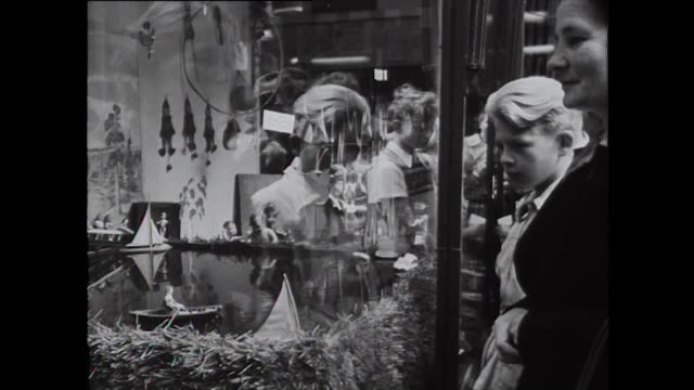 Crowds fill the streets of Helsinki as people look at Olympic themed window displays in shops 1952