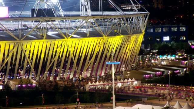 crowds flow out of the london 2012 olympic stadium after a busy day of athletics the stadium glowing yellow timelapse olympic stadium crowds at... - 2012年ロンドン夏季オリンピック点の映像素材/bロール