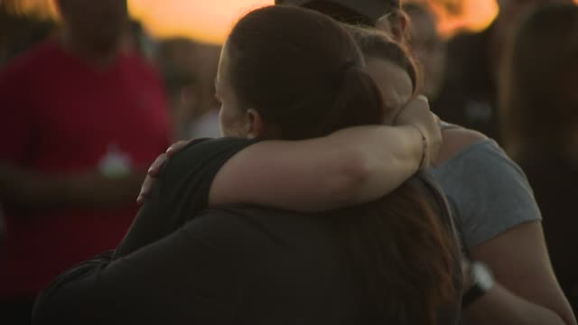 crowds gather and people embrace at a vigil for the victims of the parkland/valentine's day massacre - trauernder stock-videos und b-roll-filmmaterial