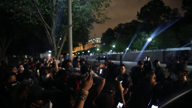 crowds gather and talk to each other about the situation while a member of security services stands over wearing a protective mask as demonstrators... - lafayette square washington dc stock videos & royalty-free footage