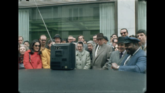crowds gather around a television on a car along the streets of new york city to watch the landing of apollo 13 from space. - splashdown stock videos & royalty-free footage