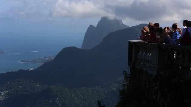 vidéos et rushes de crowds gather at an overlook beneath the christ the redeemer statue at corcovado on march 28, 2013 in rio de janeiro, brazil. rio de janeiro:... - corcovado