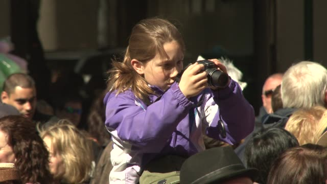 crowds gather in front of st. patrick's cathedral to witness the parade of bonnets and costumes / young girl photographs participants from her... - witness stock videos & royalty-free footage