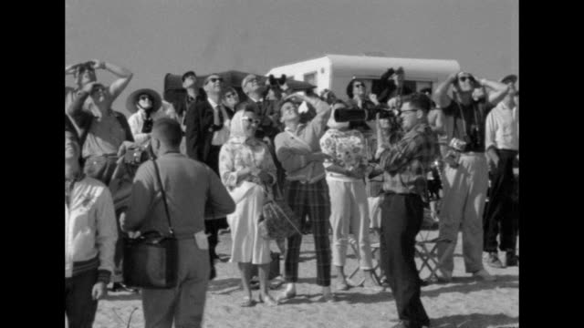 crowds gather on the beach to watch the launch of the friendship 7 at cape canaveral, florida. - space exploration stock videos & royalty-free footage