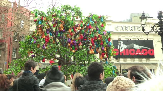 crowds gather to throw bags of luck onto a nearby tree to mark the start of the chinese new year, year of the dragon. atmosphere - lucky bags at... - dragon tree stock videos & royalty-free footage