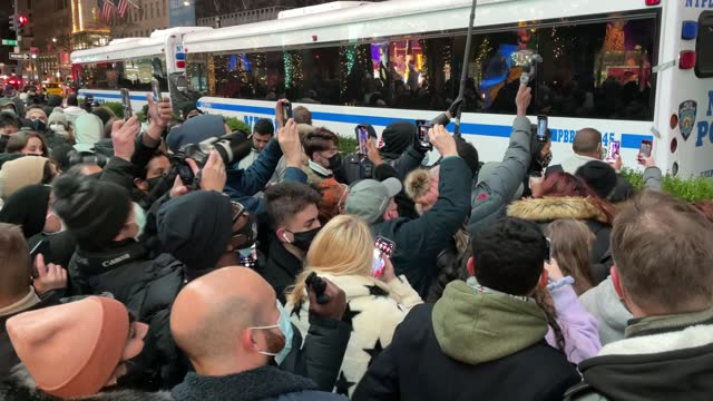 crowds gather to try view the rockefeller center christmas tree lights being turned on. views were blocked by nypd barriers, busses and garbage bags... - illuminazione dell'albero di natale del rockefeller center video stock e b–roll