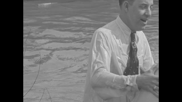 right crowds gathered around river watch woman being baptized by immersion in mississippi river / ms woman is baptized by reverend russell ridgeway... - 礼拝点の映像素材/bロール
