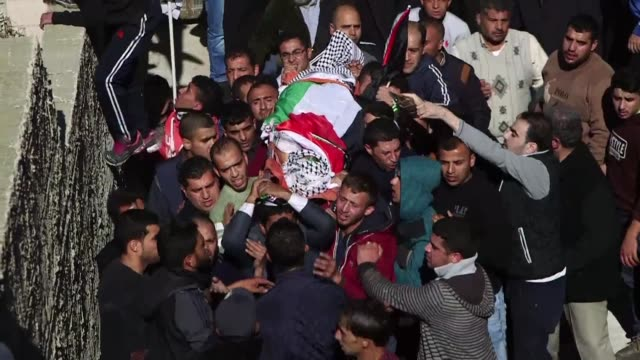 Crowds gathered in the West Bank village of Qusra on Saturday for the funeral of a Palestinian shot dead earlier in the week by an Israeli settler...