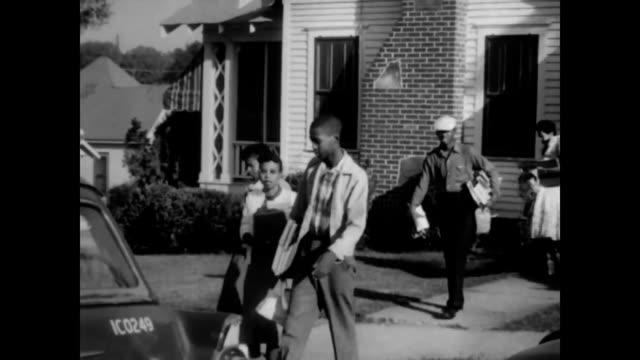 crowds gathered to watch 'little rock nine' be escorted to school / national guardsmen helping students into cars - jim crow laws stock videos & royalty-free footage