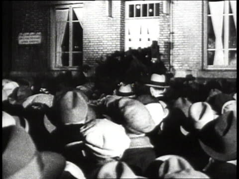 Crowds gathering outside of building / Lindbergh and Ambassador Herrick waving from balcony / crowds cheering Lindbergh
