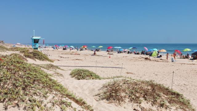 crowds having fun at carpinteria state beach - cabina del guardaspiaggia video stock e b–roll