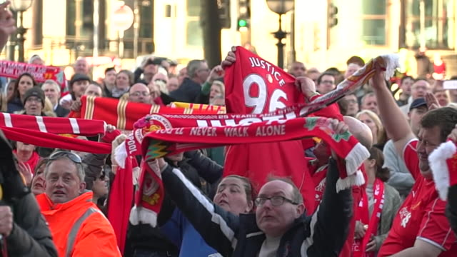 crowds holding up liverpool scarves and singing 'you'll never walk alone' outside st george's hall after the hillsborough inquest rules the victims... - liverpool england stock-videos und b-roll-filmmaterial