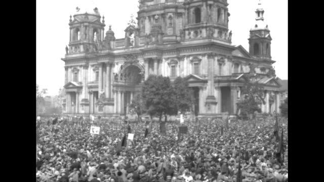 crowds in berlin streets during communist celebration of may day / pan across crowd to tilt up ext berlin cathedral in background / man wearing cap... - austria stock videos & royalty-free footage